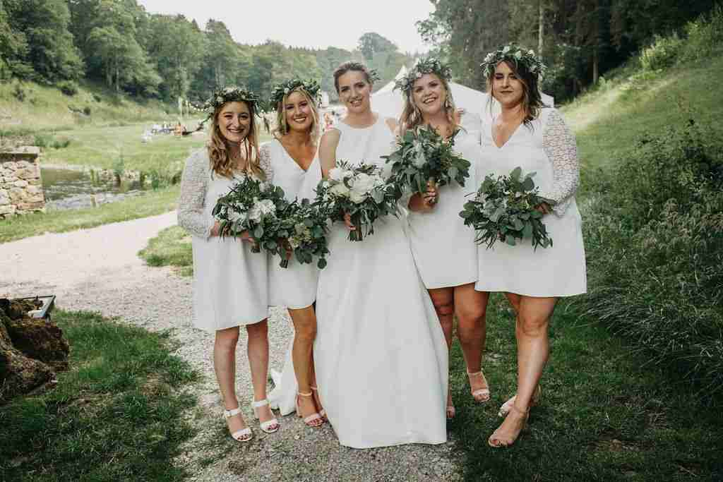 Beautiful bride with sleek updo and bohemian bridesmaids wearing flower crowns.