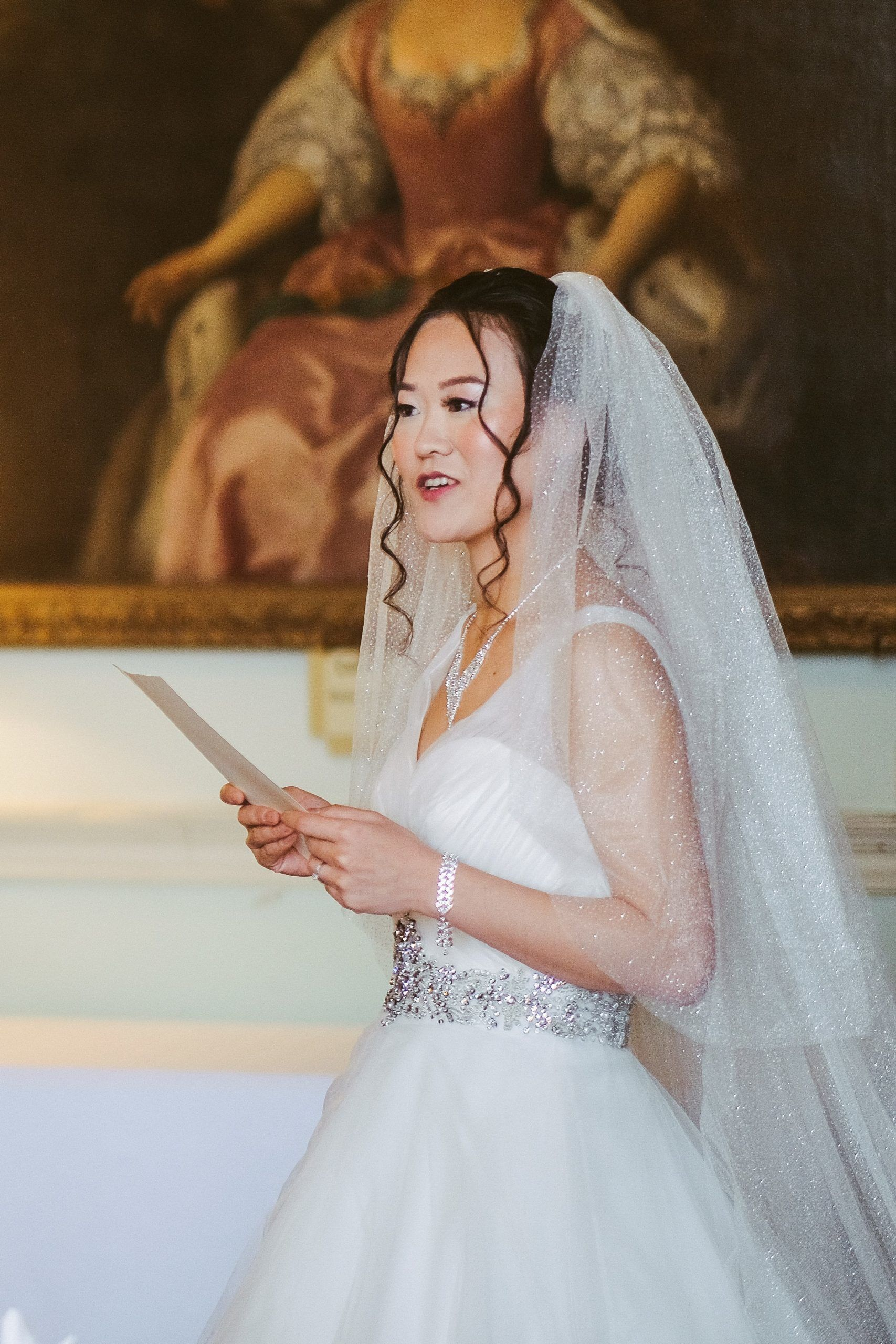 Bride gives speech, showing off natural, glowing bridal makeup and loosely curled wedding day updo with veil.