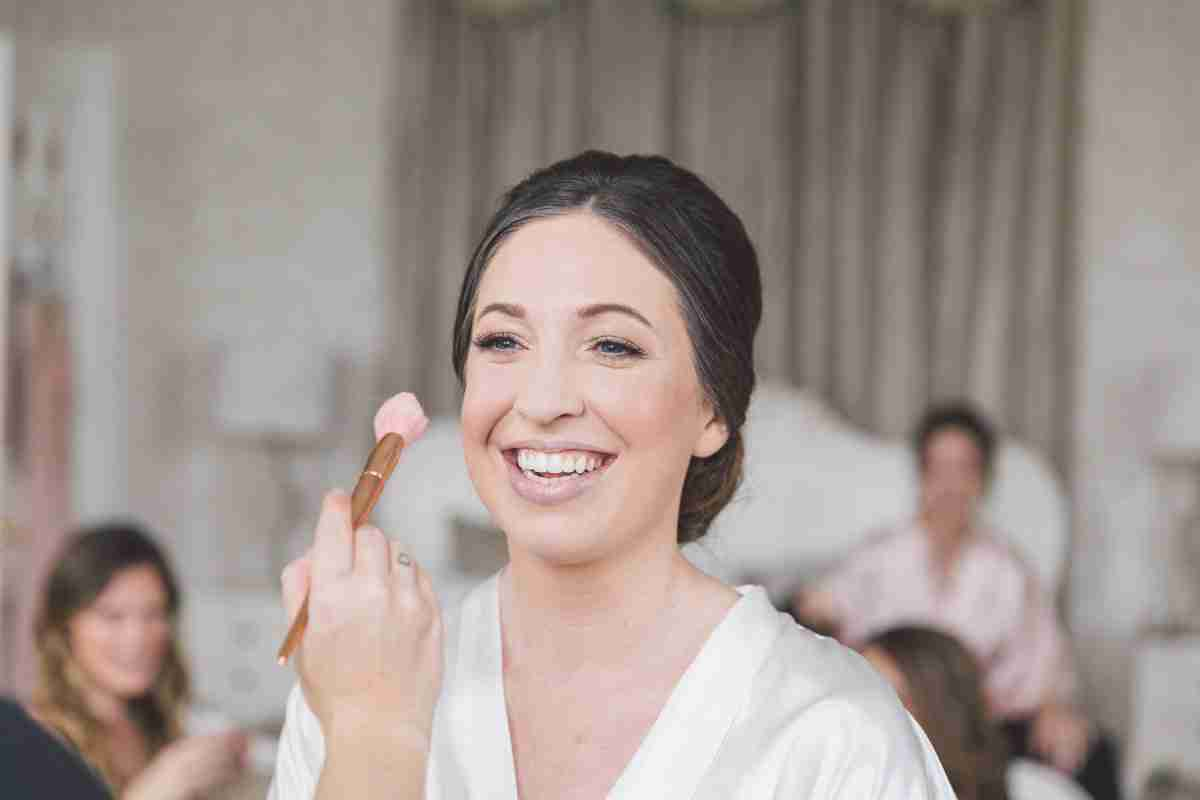 MUBYLEIGH - Hair & Makeup Artist adds blusher to smiling North East brides makeup on wedding day.