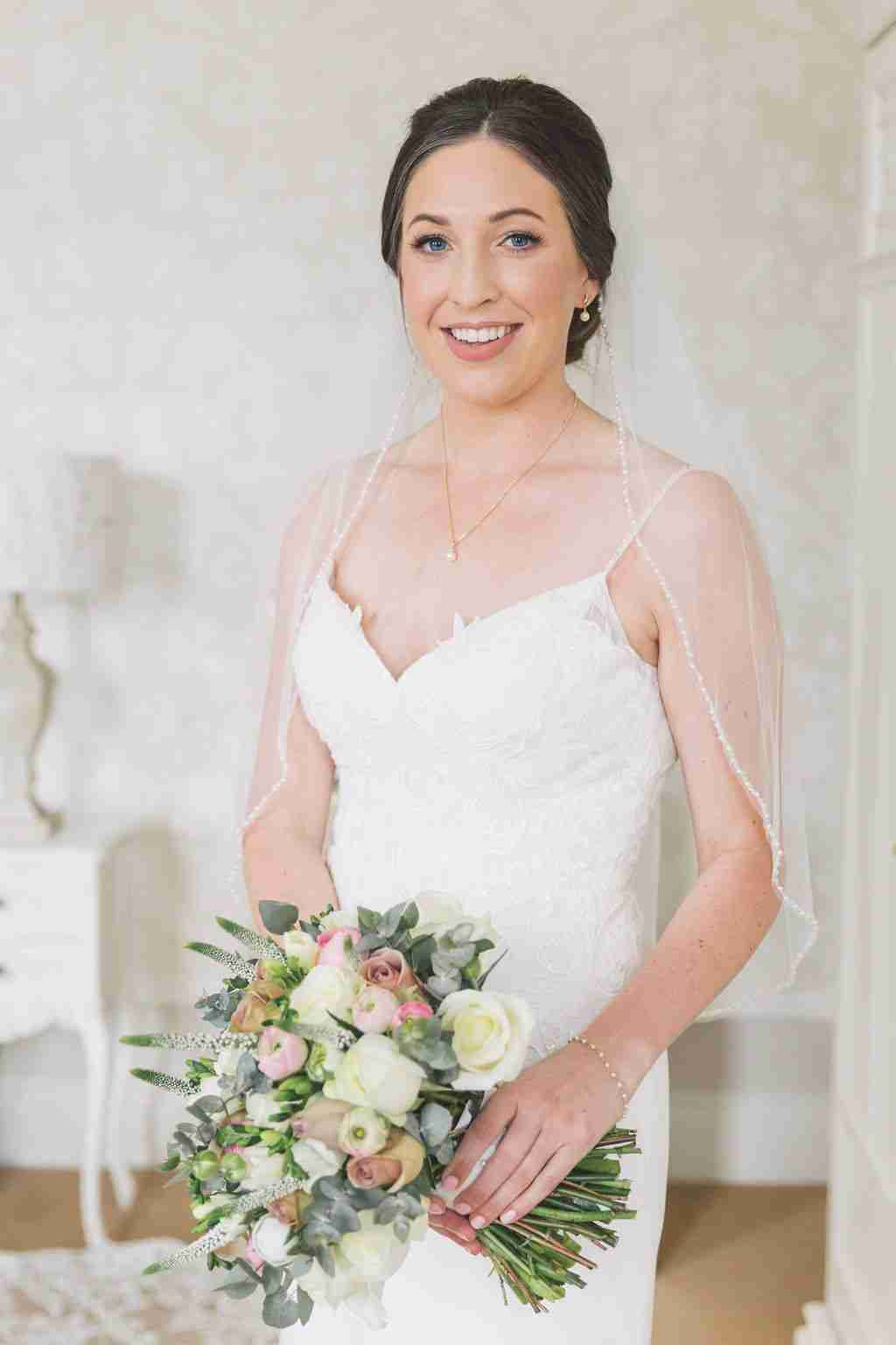 Bride with natural, wedding makeup and sleek bridal updo poses with bouquet.