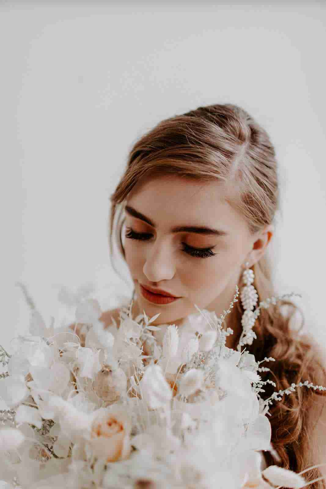 Modern bride holds dried floral bouquet below chin with eyes closed, showing smokey eye makeup and fluffy individual lashes. Bride's hair and makeup is flawless, glowing, warm toned.