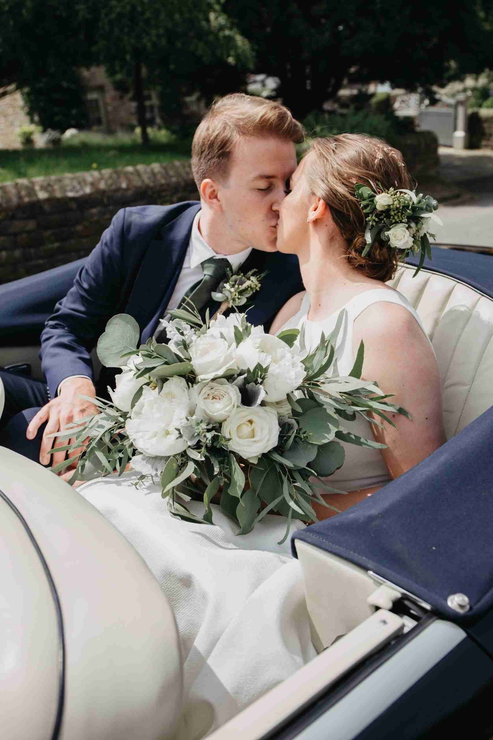 Real bride kisses groom, showing off loose, curled updo with foliage flower comb.