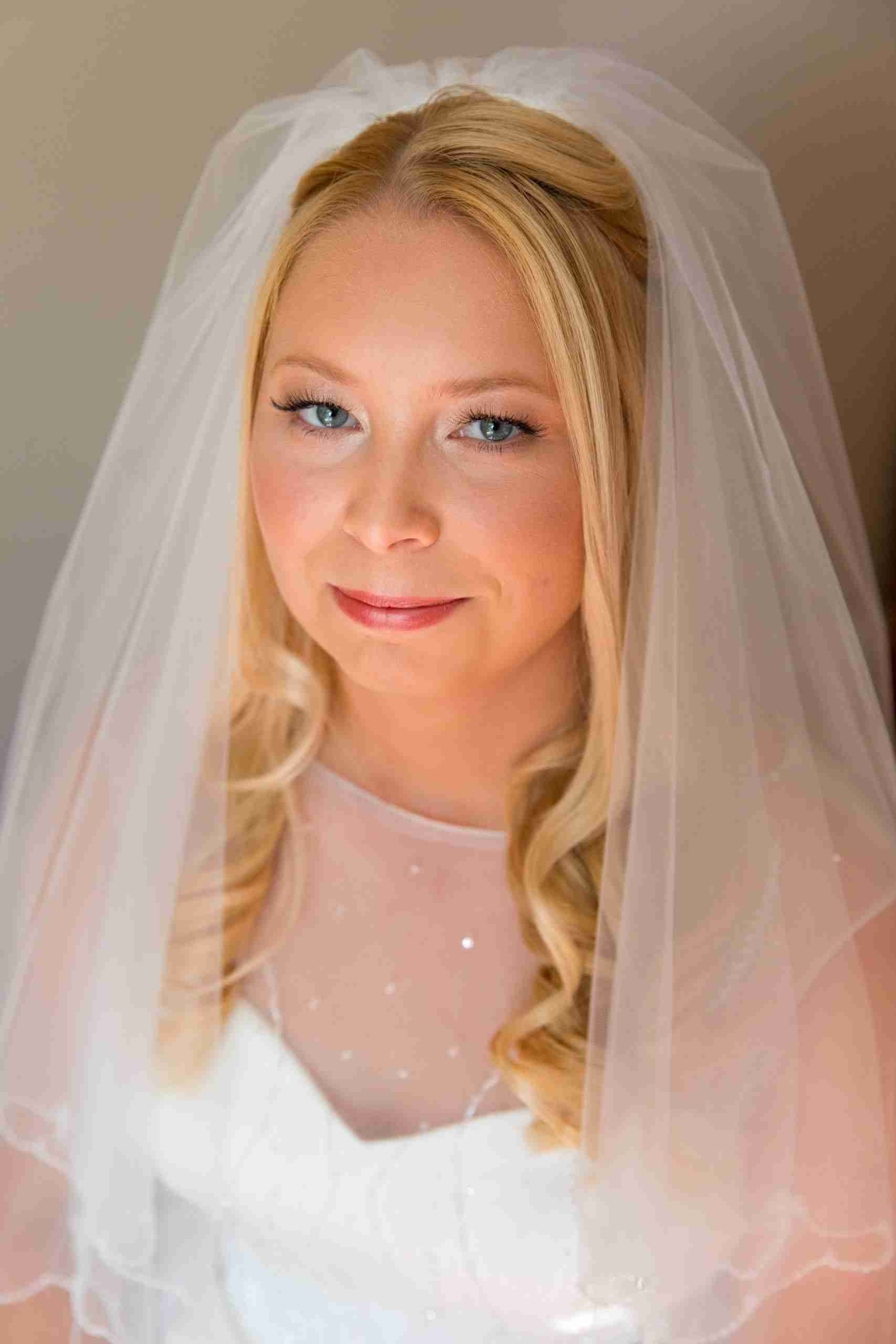 Close-up portrait of blonde haired, blue eyed bride on her wedding day. Bride wears a loosely curled, half-up, half-down hairstyle with an elbow length veil and natural, glowing makeup.