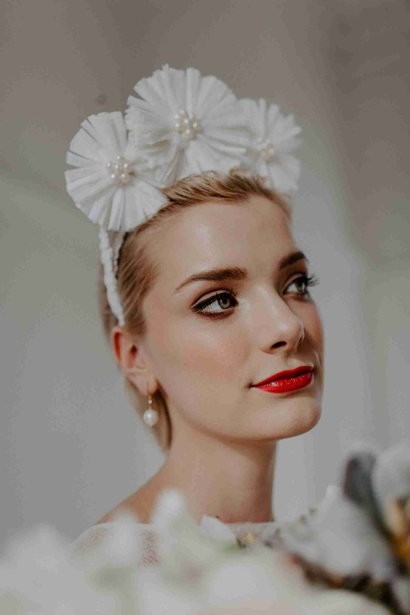 Modern bride poses in statement floral pearl headpiece. Beautiful bridal hair and makeup with a bold red lip.