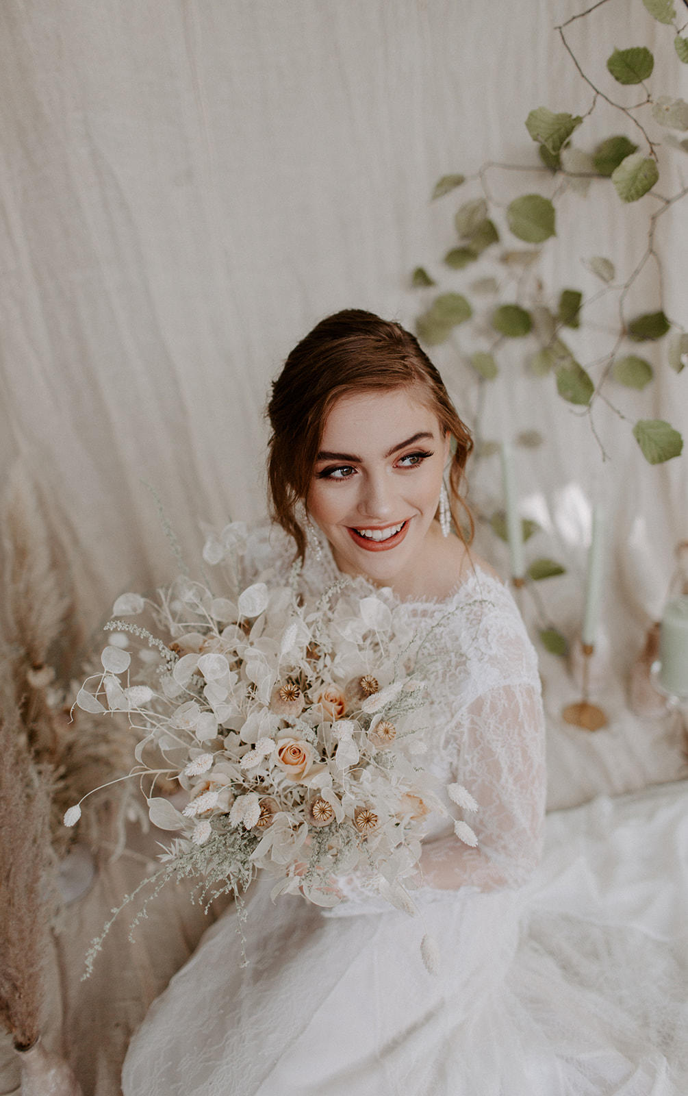 Modern, luxe bridal hair and makeup on smiling bride holding dried floral bouquet.