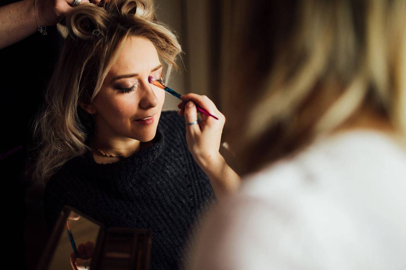 Behind the scenes photo taken at Skelwith Bridge Hotel in The Lake District, showing mubyleigh applying mascara flawless bride's eyelashes. Makeup created by Yorkshire based, professional Hair Stylist & Makeup Artist mubyleigh.