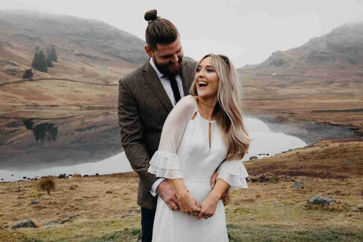 Elopement wedding. Wild, bohemian bride with long, blonde hair style and bearded groom pose in front of Blea Tarn, Lake District.