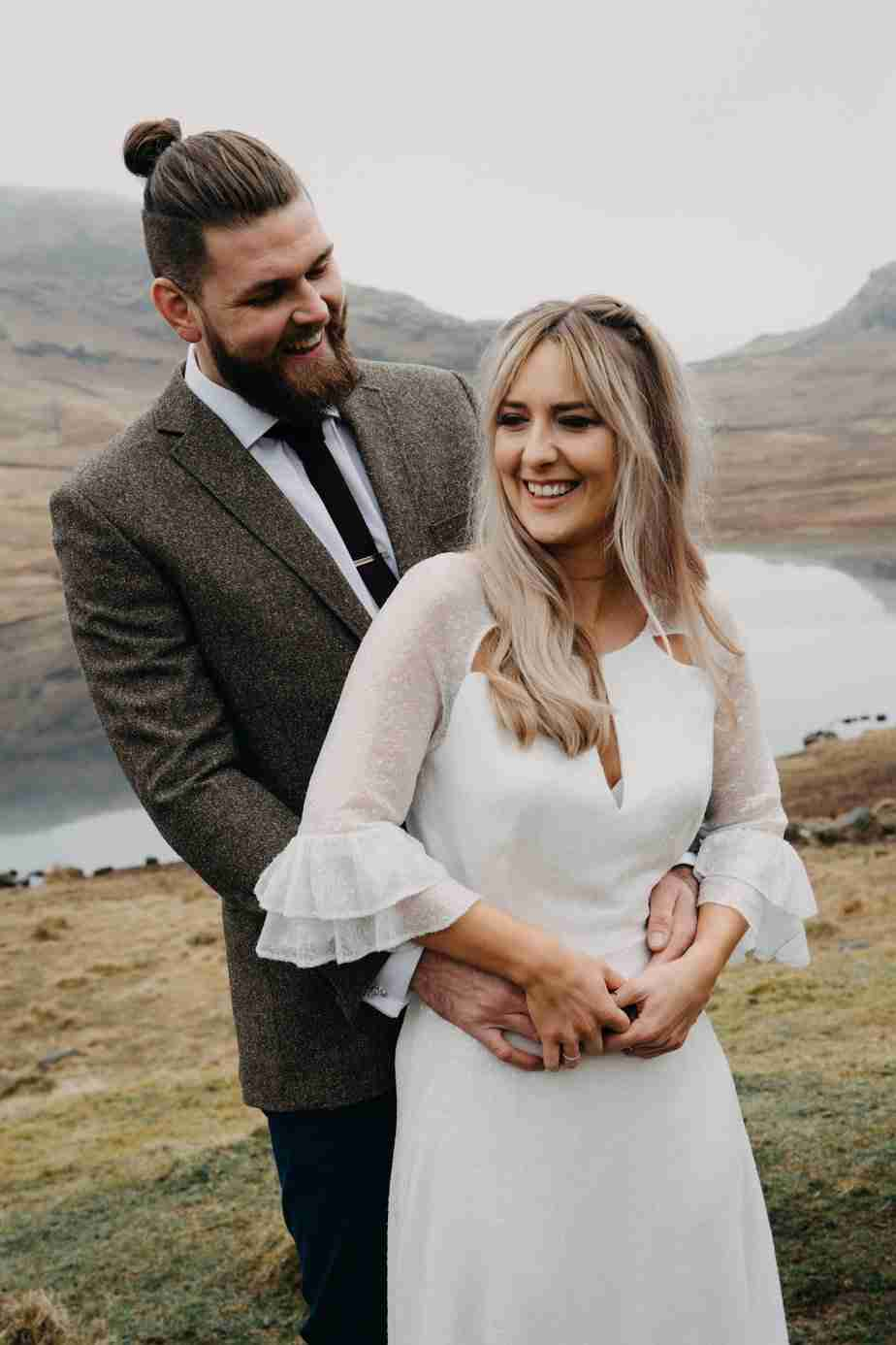 Blonde bride with half-up, half-down, bohemian, hairstyle laughs with groom at elopement wedding in The Lakes.