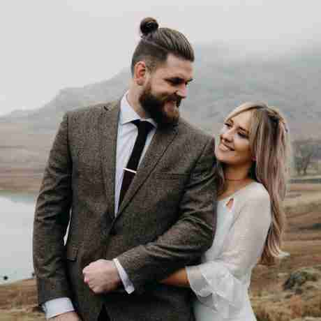 Blonde, bohemian bride wearing sequin wedding dress cuddles groom beside Blea Tarn, Lake District.