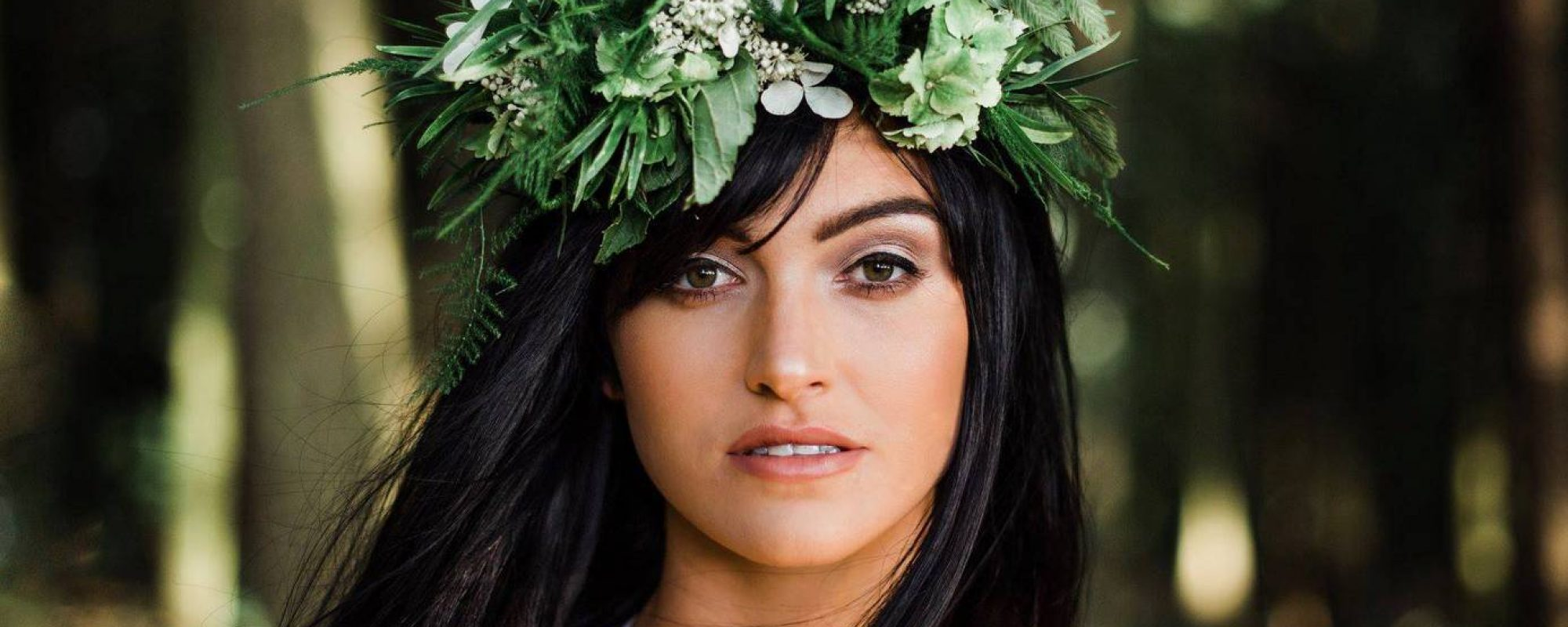 Closeup of Bride during woodland wedding photo shoot. Bride has tousled long dark black hair and a sweeping fringe. Bride has flawless skin, soft contour and bold blusher. Highlighter is used to accentuate her features, especially her cheekbones and eyelids. She has a soft smokey eyeshadow in her crease, a shimmering shadow on the lid and long, thick eyelashes. Black liner is applied to the lash line to further enhance the eyes and the look is finished off with a glossy deep pink lip. Bride wears a foliage flower crown by Elle Flowers UK. Hair and makeup created by professional, freelance Hair & Makeup Artist mubyleigh.