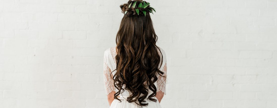 Boho bride with long, dark, curly hairstyle and plaited crown braid adorned with foliage. Wearing a Luna Organics lace wedding dress. Hair and makeup created by Yorkshire based, professional Hair Stylist & Makeup Artist mubyleigh.